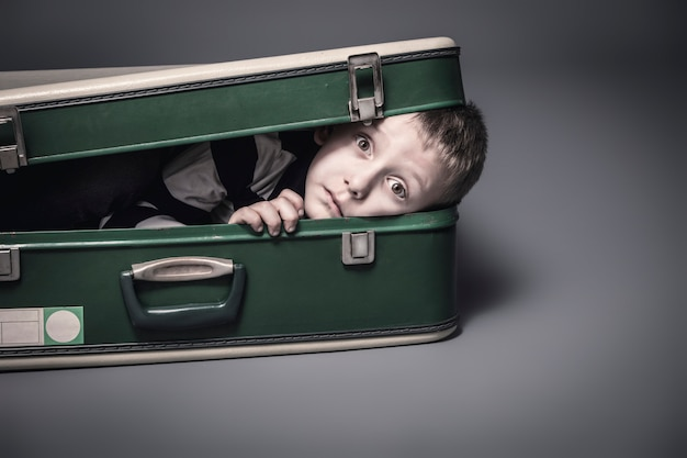 少年は古いスーツケースに隠れています