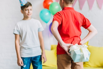 Boy hiding birthday gift from his friend