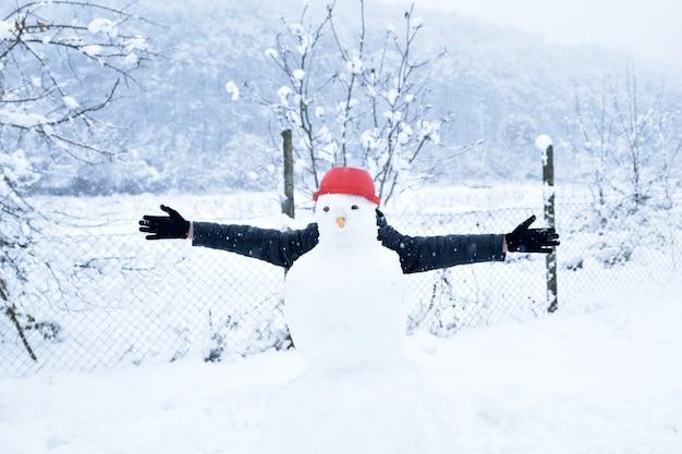 Boy hiding behind a snowman, fun winter activities