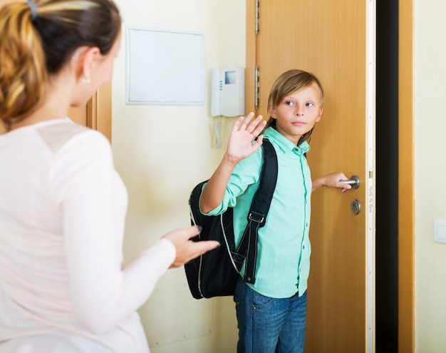 Boy and his mother staying near flat entrance