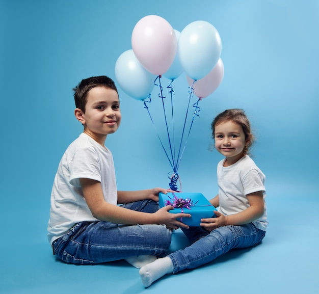 Boy and his sister dressed alike sit on blue surface and hold a blue gift with pink bow and look at front