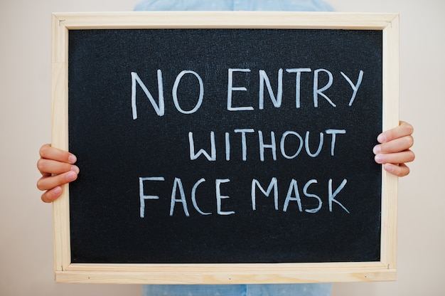 Boy hold inscription on the board with the text no entry without face mask