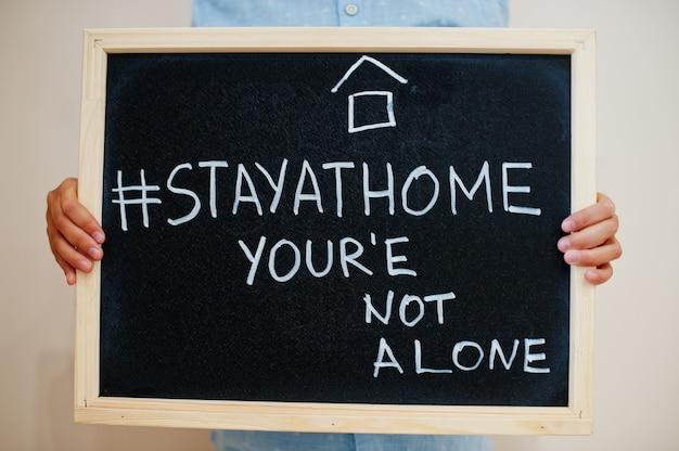 少年はボードに「stayhomehashtag」というテキストの碑文を持っています、あなたは一人ではありません