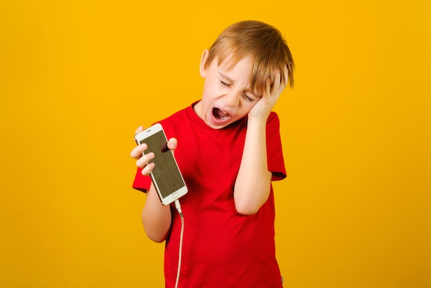 Boy holdimg a phone with a defective charging cord.