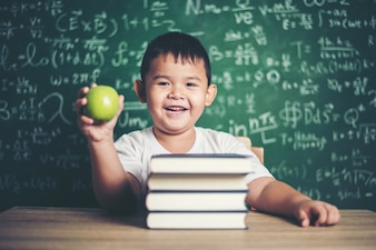 Boy holding a apple in the classroom