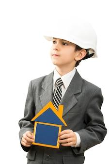 彼の頭の建設用ヘルメットに段ボールの家を手に持っている少年、彼自身は建築家です