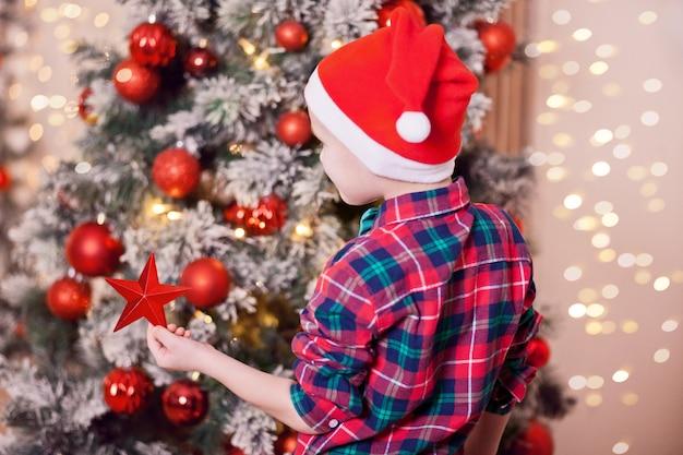 クリスマスツリーからクリスマスの大きな星を持つ男の子 Premium写真