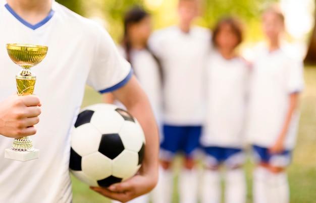 Мальчик держит золотой трофей рядом с расфокусированными товарищами по команде