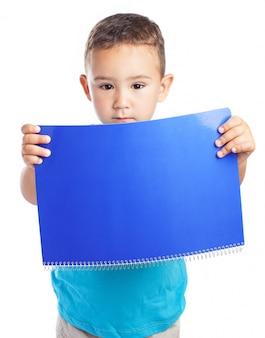 少年は彼の前にノートブックを保持します