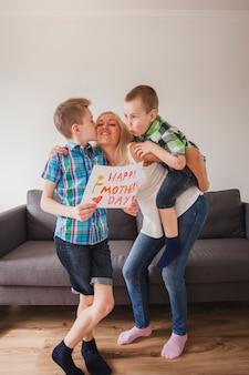 ポスターを持って母親にキスをする少年