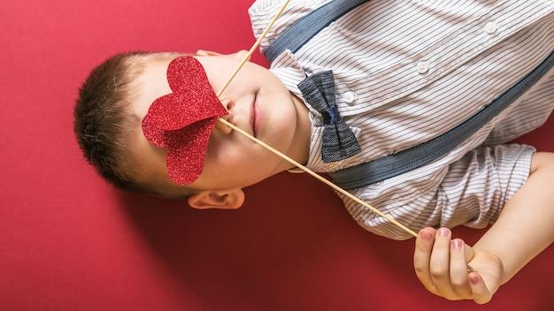 사랑, 가족, 희망의 눈 상징에 붉은 마음을 잡고 소년.