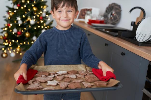 自家製ジンジャーブレッドクッキーがいっぱい入ったトレイを持っている少年