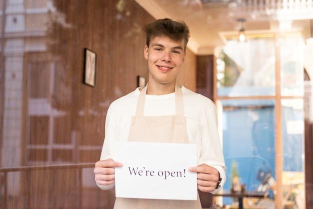 Мальчик держит табличку «мы открыты» после окончания карантина