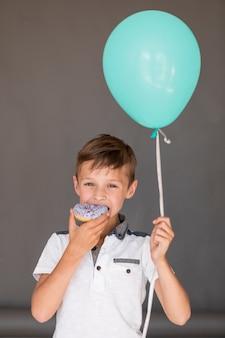 Boy holding a balloon while eating a doughnut