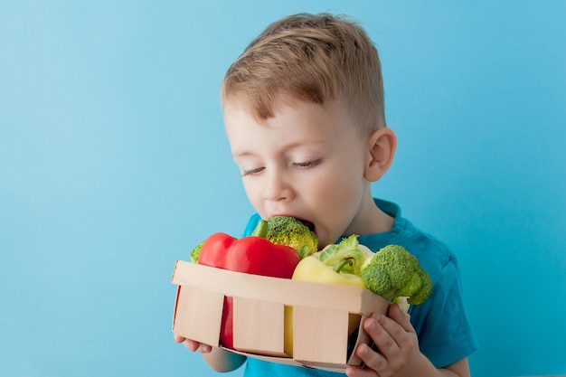 Мальчик держит корзину со свежими овощами на синем фоне. веганская и здоровая концепция.