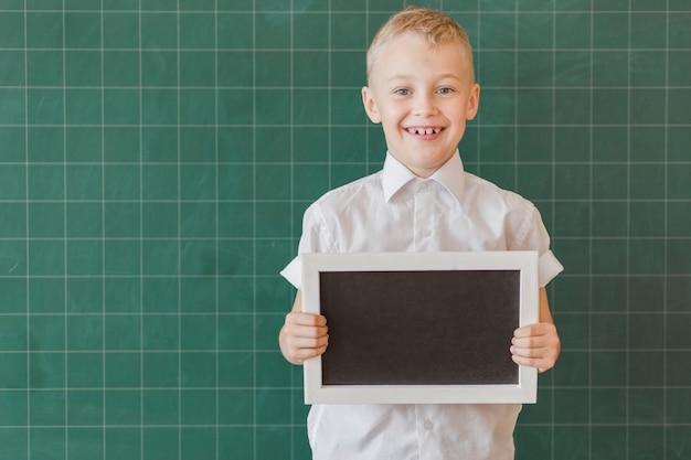Boy holding blackboard near chalkboard