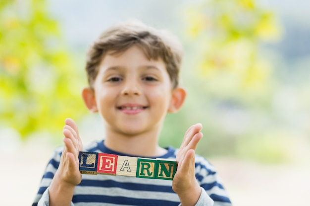 Boy holding blocks in park which reads learn
