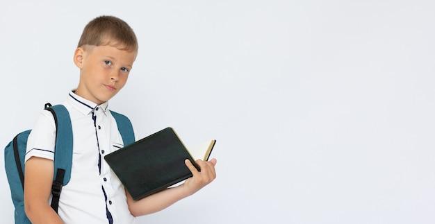 コピースペースバナーで白い表面に分離された本を保持している少年