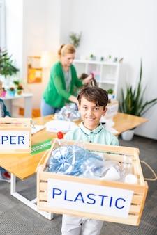 Мальчик держит коробку. сияющий красивый темноволосый мальчик держит коробку с пластиком после сортировки мусора в школе