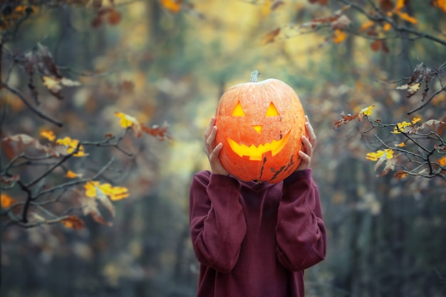 Boy holding carved pumpkin for halloween in front of his head in dark autumn forest.