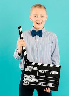 Boy holding clapperboard medium shot