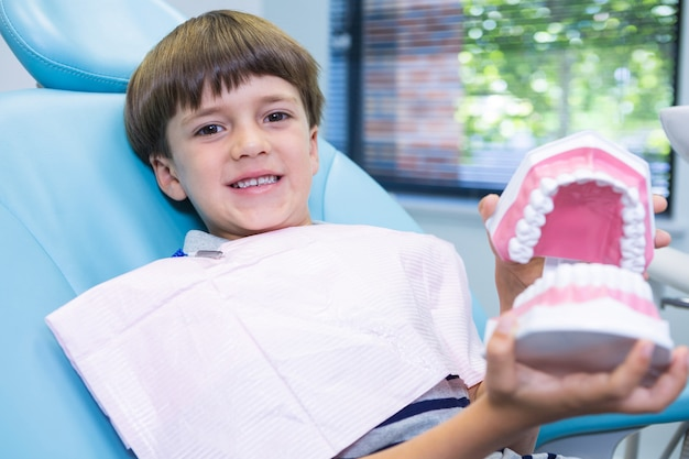Boy holding dental mould while sitting on chair at medical clinic