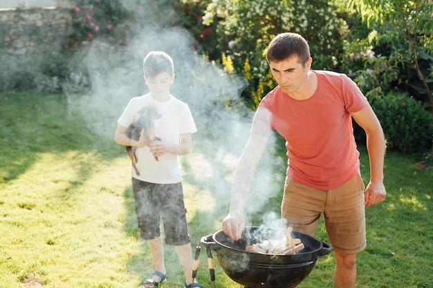 公園で食べ物を準備する彼の父の近くに立っている犬を持つ男の子