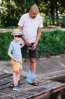 Boy holding fishing net standing with his father on pier