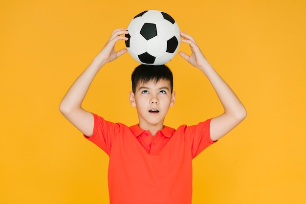 Boy holding a football ball on his head