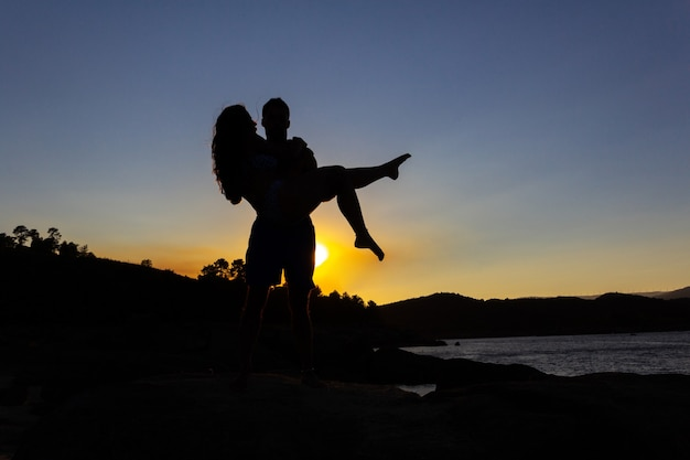 Boy holding girl in his arms at sunset in autumn. copy space. backlight. love.