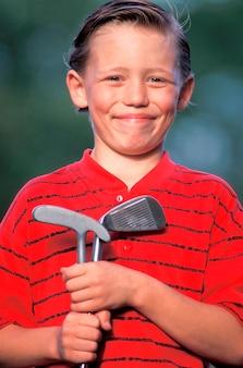 Boy holding golf clubs