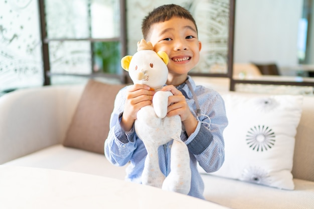 그의 곰 문을 들고 방을 떠나는 미소 소년