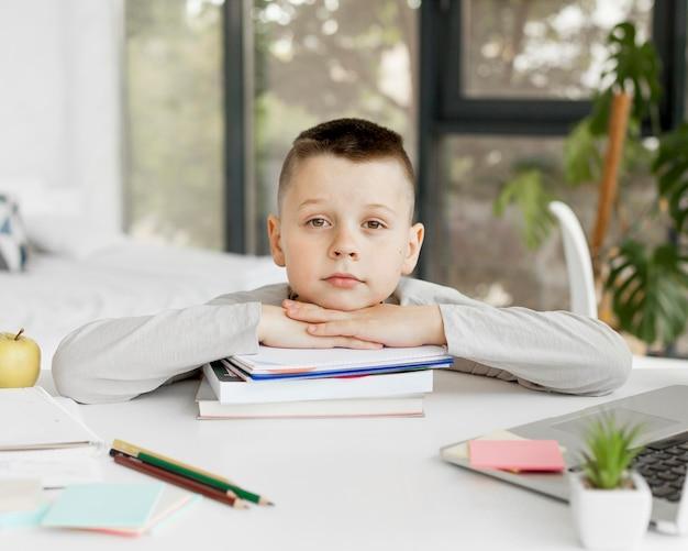 Мальчик держит голову на кучу книг