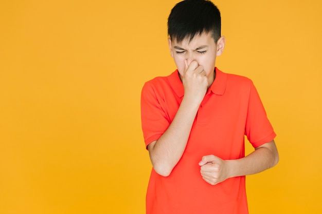 Boy holding his nose because of something stinky