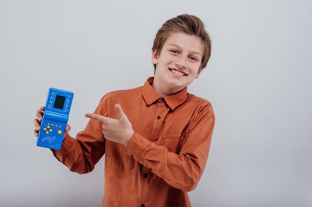 흰색 배경에 고립 된 아이 손에 파란색 테트리스 게임을 손에 들고 소년 오래된 가제트