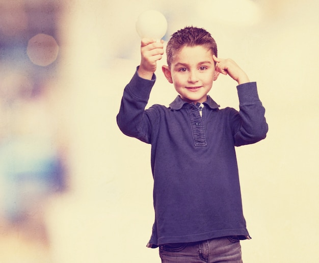 Boy holding a light bulb and touching his forehead