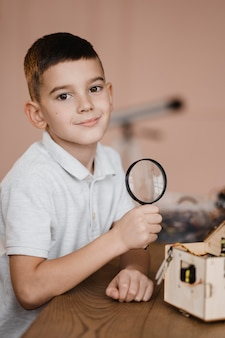 Boy holding a magnifier in class