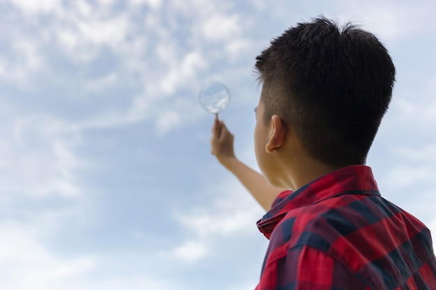 Boy holding a magnifying glass and looking to the sky