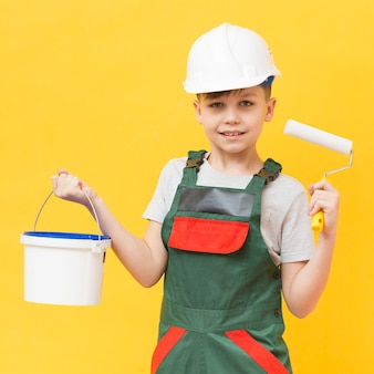 Boy holding painting roller medium shot