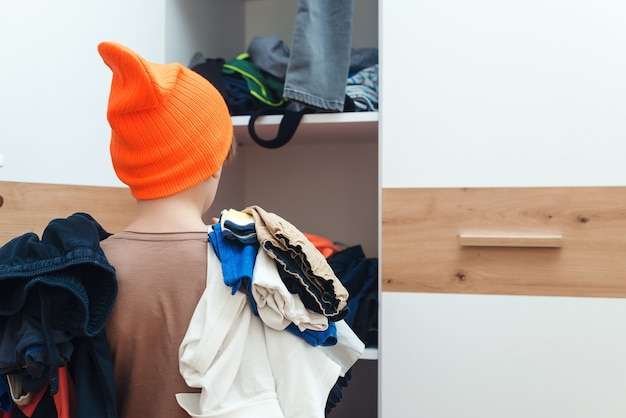 Boy holding pile of dirty clothes. messy home kid's room. home chores housework.