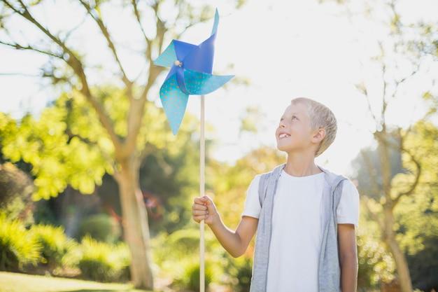 Boy holding a pinwheel in park