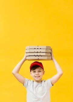 Мальчик держит пиццу коробки копией пространства