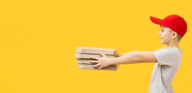 Мальчик держит пиццу коробки сбоку
