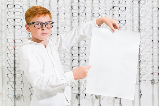 Boy holding and pointing at black white paper in optics shop