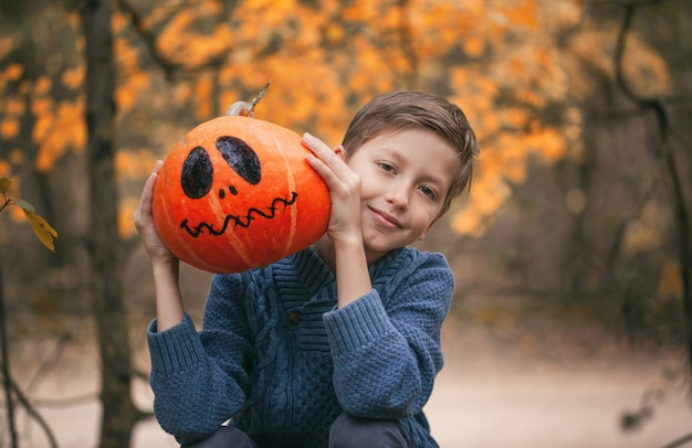 Boy holding a pumpkin. the concept of holidays. preparing for halloween.