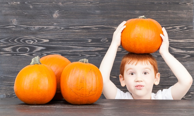 Boy  holding a pumpkin over his head