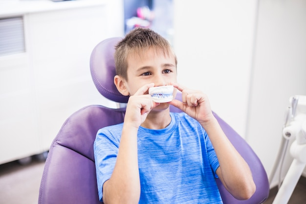 Boy holding teeth plaster mold in front of his mouth