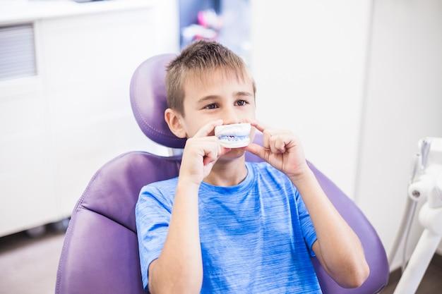 彼の口の前に歯の石膏型を保持している少年