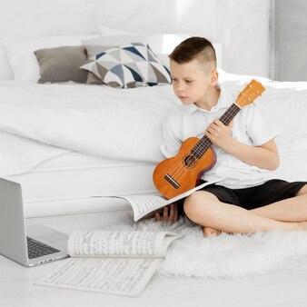 Boy holding an ukulele guitar