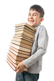 少年は古い本の山を持って笑っている